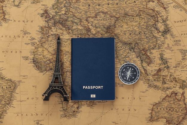 旅行の計画。古い地図上のエッフェル塔の置物、コンパス、パスポート。冒険の概念