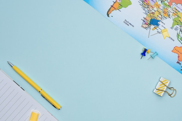 旅行計画フラットコピースペースを置きます。文房具と青色の背景の地図。