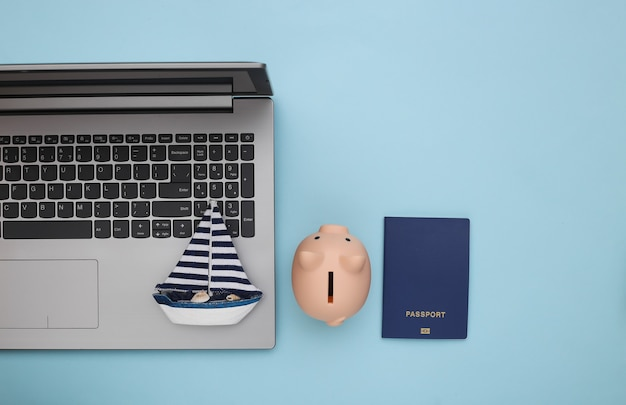 Travel planning. laptop and sailboat, piggy bank, passport on blue background. top view. flat lay