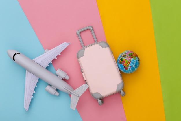 여행 계획. 미니 장난감 여행 가방, 비행기 및 지구본