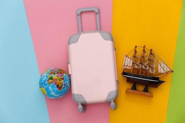 여행 계획. 미니 장난감 여행 가방, 선박 및 지구본