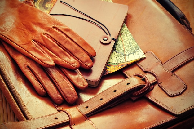 Travel planning note map leahter briefcase and gloves on wooden background