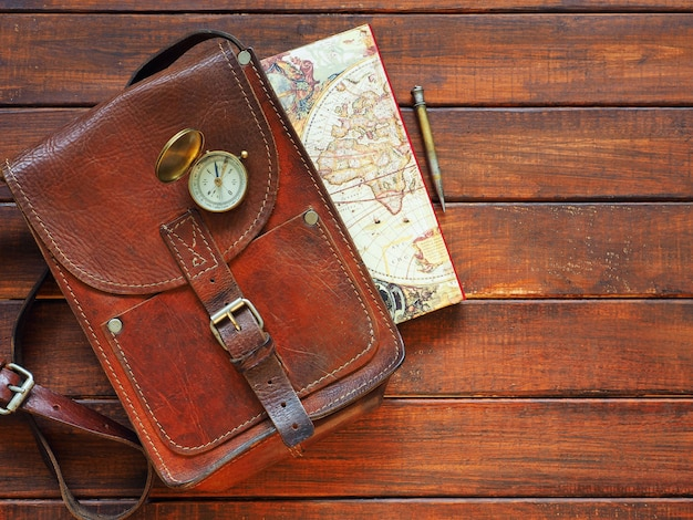 Travel planning old compass map leahter briefcase and pen on wooden background