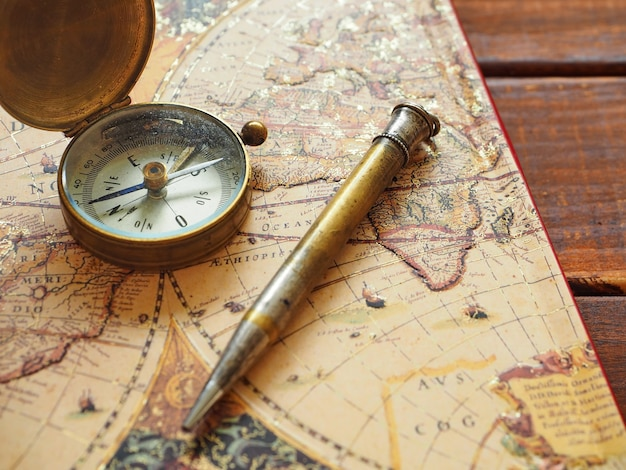 Travel planning old compass map and pen on wooden background