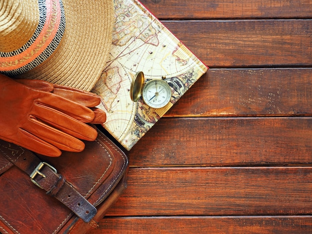 Travel planning old compass map straw hat leahter briefcase and gloves on wooden background