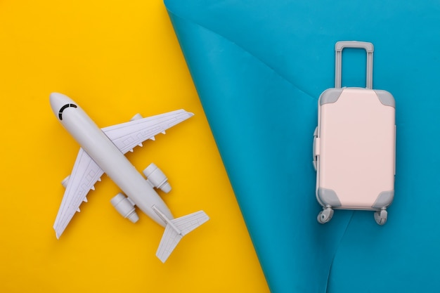 Travel planning. toy travel luggage and air plane on blue yellow. flat lay.