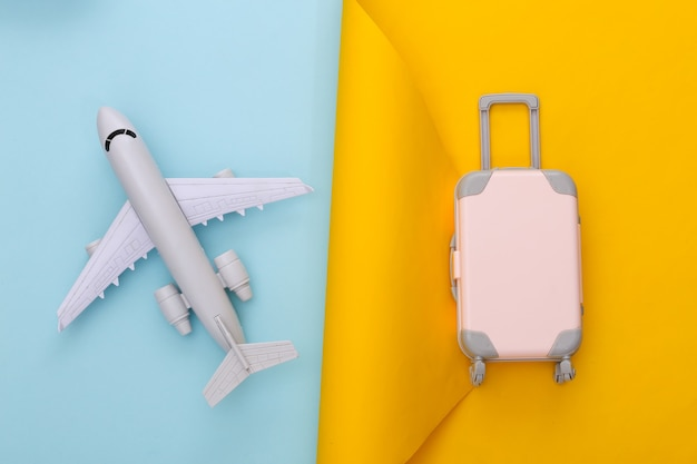 Travel planning. toy travel luggage and air plane on yellow blue. flat lay
