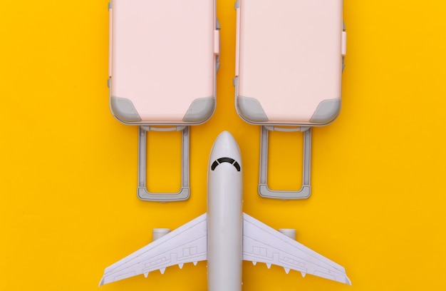 Travel planning. two toy travel luggage and air plane on yellow. flat lay
