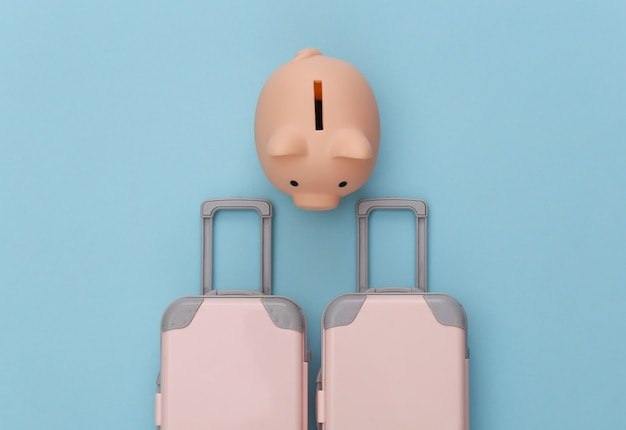 Travel planning. two toy travel luggage and piggy bank on  blue pastel