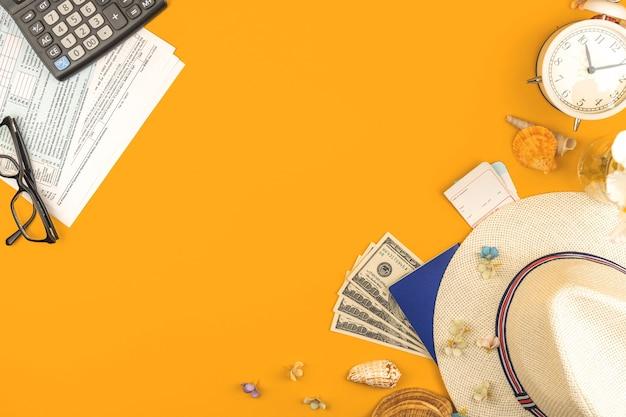 旅行準備ワークスペース、航空会社の搭乗券、お金の入ったパスポート、麦わら帽子と熱帯の花々、コピースペースと上面写真を使って将来の旅行のためのお金を計算する