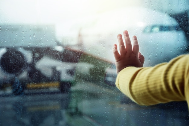 Travel in rainy day concept. closeup of children's hand on window in airport