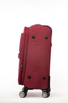 白い背景で隔離の赤いスーツケースを旅行します。