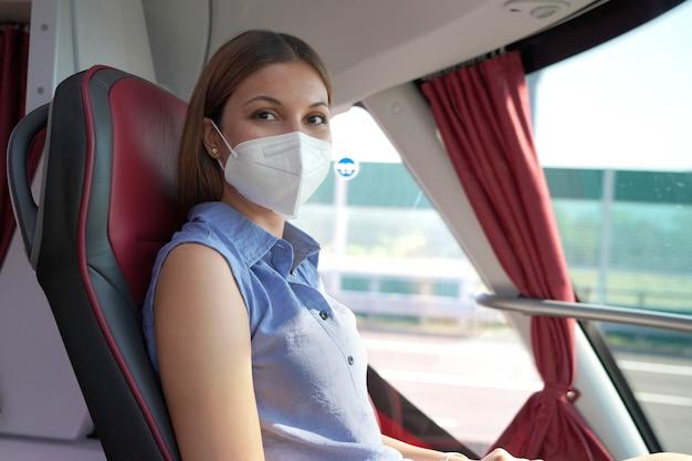 安全に旅行する。カメラを見ているバスの美しい笑顔の旅行者の女性。