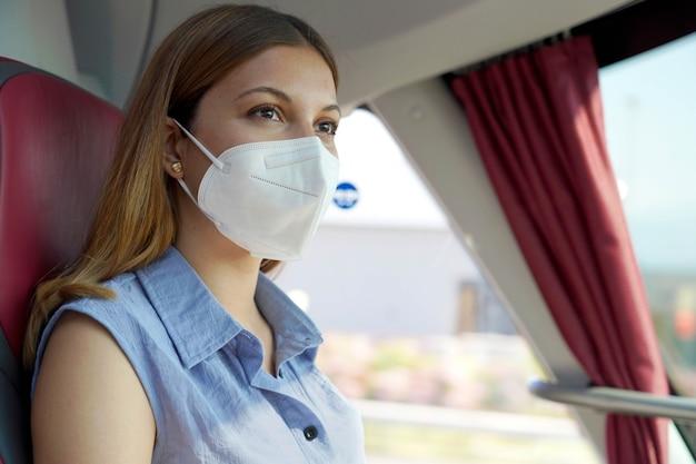 公共交通機関で安全に旅行してください。彼女の旅行中にバスの窓を通して見ているkn95ffp2保護フェイスマスクを持つ若い女性のクローズアップ。