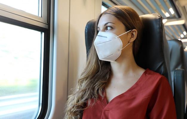公共交通機関で安全に移動します。電車の窓から見ているフェイスマスクを持つ若い女性。