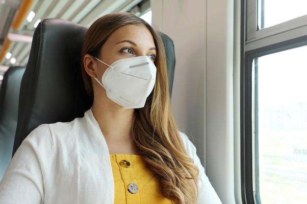 公共交通機関で安全に移動します。電車の窓から見ているkn95 ffp2フェイスマスクを持つ若い女性。防護マスク旅行で乗客を訓練し、窓越しに見ているビジネスクラスに座っています。