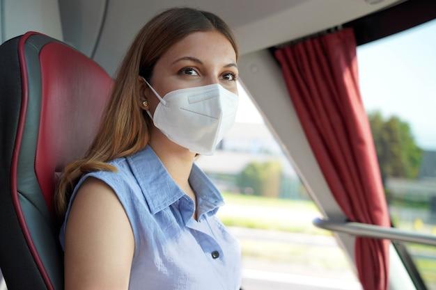 公共交通機関で安全に旅行してください。彼女の旅行中にバスの窓を通して見ているkn95ffp2保護フェイスマスクを持つ若い女性。
