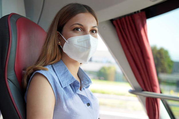 Travel safely on public transport. young woman with kn95 ffp2 protective face mask looking through bus window during her journey.