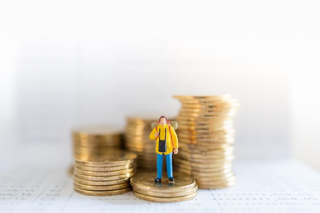 Travel saving and planing concept. traveler miniature people figure with backpack standing on stack of gold coins on bank passbook with copy space.