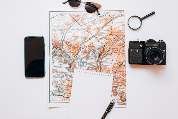 Travel set: map, sunglasses, camera, notebook, pen, phone, magnifier