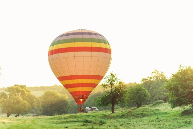 Travel and sport. multi colored striped hot air balloon flying above valley in sky at sunrise.