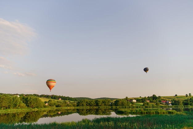 Travel and sport. two multi colored hot air balloons flying above lake in sky at sunrise.