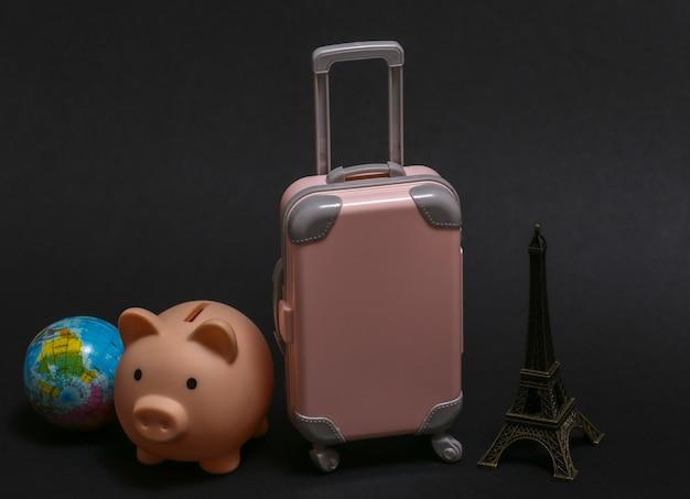静物を旅する。黒の背景にエッフェル塔、地球儀、貯金箱の小像が付いたミニプラスチック製の旅行スーツケース。
