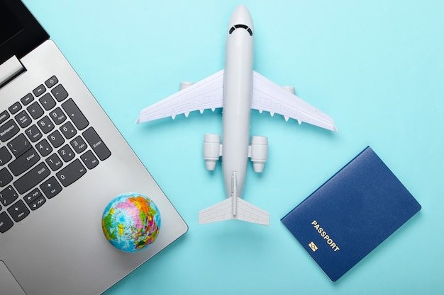 Travel still life. online booking. emigration. laptop, globe, plane and passport. tourist accessories on blue background. top view. flat lay
