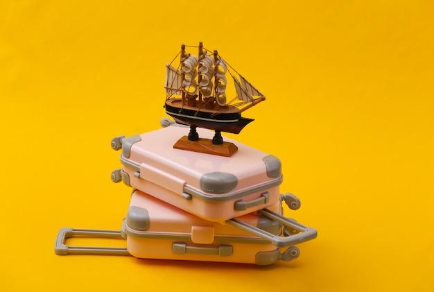 Путешествие натюрморт, отпуск или туристическая концепция. два мини-чемодана для путешествий и корабль на желтом