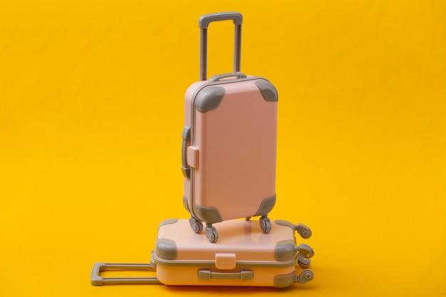 Путешествие натюрморт, отпуск или туристическая концепция. два мини-чемодана для путешествий на желтом