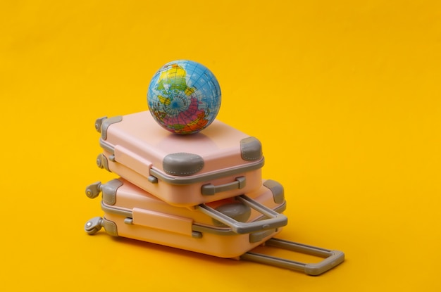 Travel still life, vacation or tourism concept. two mini travel luggage suitcase and globe on yellow