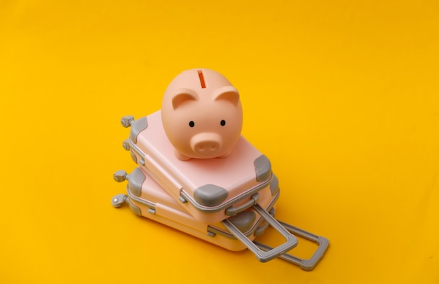 Travel still life, vacation or tourism concept. two mini travel luggage suitcase and piggy bank on yellow