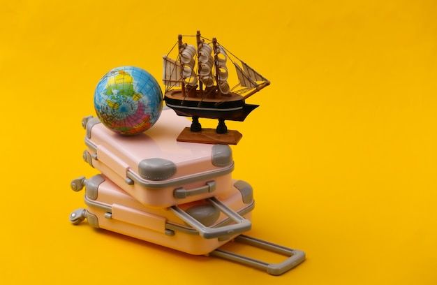 Travel still life, vacation or tourism concept. two mini travel luggage suitcase and ship with globe on yellow