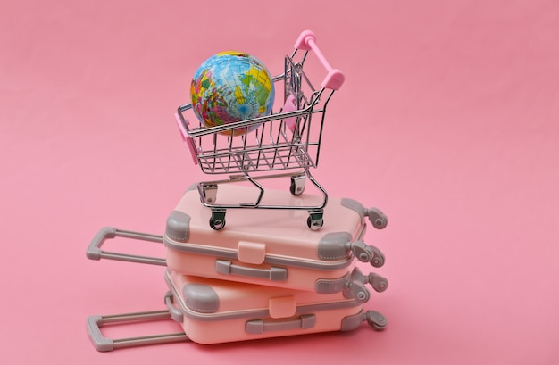 Travel still life, vacation or tourism concept. two mini travel luggage suitcase and shopping trolley with globe on pink