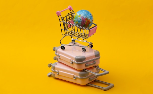 Travel still life, vacation or tourism concept. two mini travel luggage suitcase and shopping trolley with globe on yellow