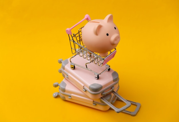 Travel still life, vacation or tourism concept. two mini travel luggage suitcase and shopping trolley with piggy bank on yellow