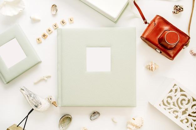 사진 앨범, 레트로 카메라, 흰색 표면에 새 조각과 함께 여행 스타일 구성