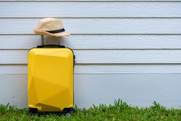Travel suitcase with hat on the ground with white wall.