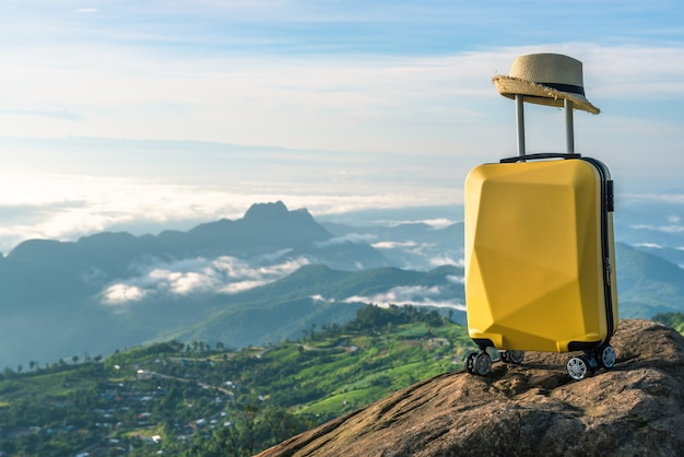 Travel suitcase with hat on the nature of beautiful mountain landscape and mist