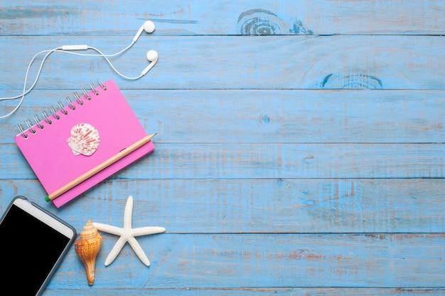 Viaggi, accessori estivi su legno blu