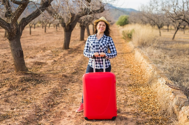 여행, 여름 및 사람들 개념입니다. 모자에 빨간 가방을 가진 여자