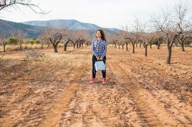 旅行、夏、人々のコンセプト-自然の表面にスタイリッシュなバックパックを持つ女性。彼女は休暇中です