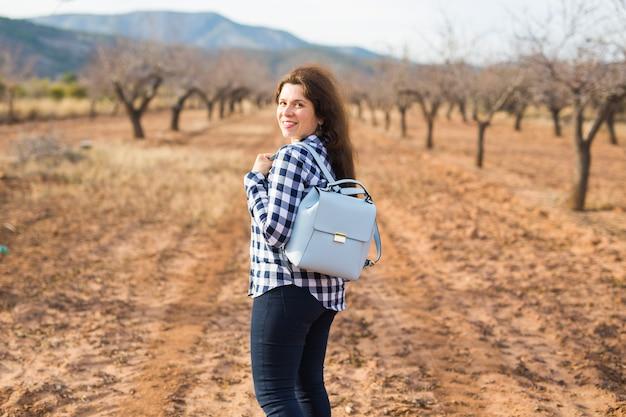 旅行、夏、人々のコンセプト。自然にスタイリッシュなバックパックを持つ女性。彼女は休暇中です