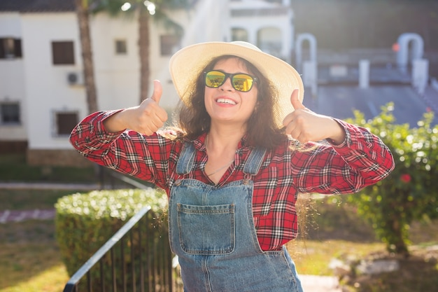 여행, 여름 및 휴가 개념입니다. 모자에 행복 한 젊은 여자는 호텔 배경 위에 엄지손가락을 보여줍니다.