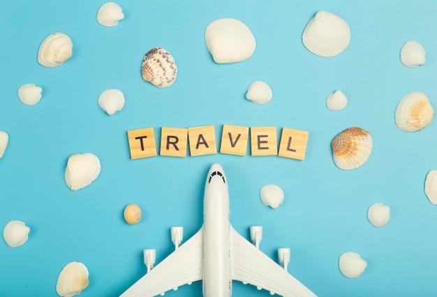 旅行の夏の背景。色付きの青い背景の飛行機と貝殻。観光休暇、リラクゼーション、夏のコンセプト。高品質の写真