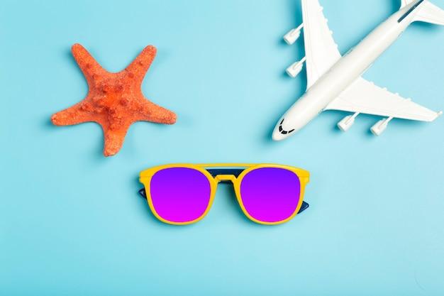 旅行の夏の背景。色付きの青い背景にサングラス、帽子、飛行機、ビーチアクセサリー。観光休暇、リラクゼーション、夏のコンセプト。高品質の写真