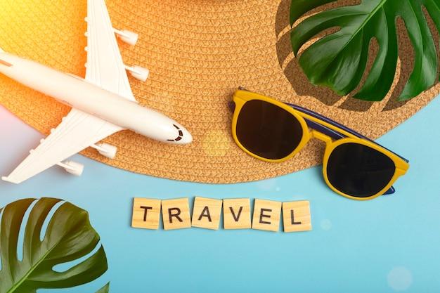 Путешествие летний фон. солнцезащитные очки, шляпа, пальмовые тропические листья, самолет и пляжные аксессуары на цветном синем фоне. туристический отдых, релаксация и летняя концепция. фото высокого качества