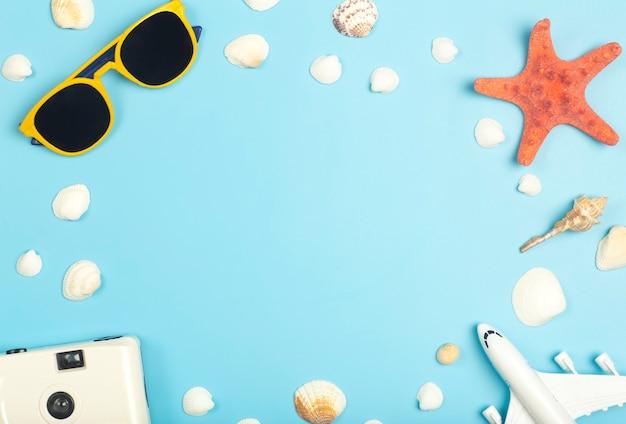 旅行の夏の背景。色付きの青い背景にサングラス、貝殻、飛行機、ビーチアクセサリー。観光休暇、リラクゼーション、夏のコンセプト。高品質の写真