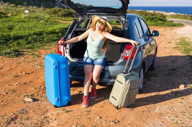 旅行、夏休み、休暇のコンセプト-車の旅でスーツケースを持った若い女性。