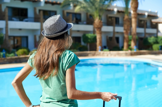 Travel, summer holidays and vacation concept - beautiful woman walking near hotel pool area with suitcase in egypt